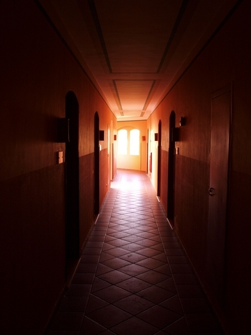 dark hallway with light streaming in through angled doors